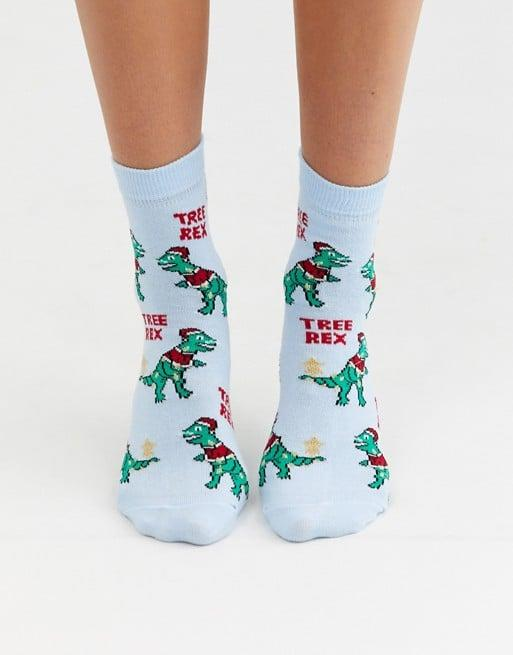 """<p>Who wouldn't love these punny <a href=""""https://www.popsugar.com/buy/ASOS-Design-Holidays-Tree-Rex-Ankle-Socks-517724?p_name=ASOS%20Design%20Holidays%20Tree%20Rex%20Ankle%20Socks&retailer=asos.com&pid=517724&price=5&evar1=fab%3Aus&evar9=36282856&evar98=https%3A%2F%2Fwww.popsugar.com%2Fphoto-gallery%2F36282856%2Fimage%2F47004932%2FASOS-Design-Holidays-Tree-Rex-Ankle-Socks&list1=shopping%2Cgifts%2Choliday%2Cgift%20guide%2Choliday%20fashion%2Cfashion%20gifts&prop13=api&pdata=1"""" rel=""""nofollow"""" data-shoppable-link=""""1"""" target=""""_blank"""" class=""""ga-track"""" data-ga-category=""""Related"""" data-ga-label=""""https://www.asos.com/us/asos-design/asos-design-holidays-tree-rex-ankle-socks/prd/13121975?clr=blue&amp;colourWayId=16530140&amp;SearchQuery=&amp;cid=25893"""" data-ga-action=""""In-Line Links"""">ASOS Design Holidays Tree Rex Ankle Socks</a> ($5)?</p>"""
