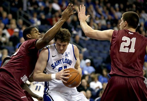 Saint Louis forward Rob Loe, center, squeezes between Saint Joseph's forwards Ronald Roberts Jr., left, and Halil Kanacevic, right, on his way to the basket during the first half of an NCAA college basketball game, Wednesday, Feb. 27, 2013, in St. Louis. (AP Photo/Jeff Roberson)