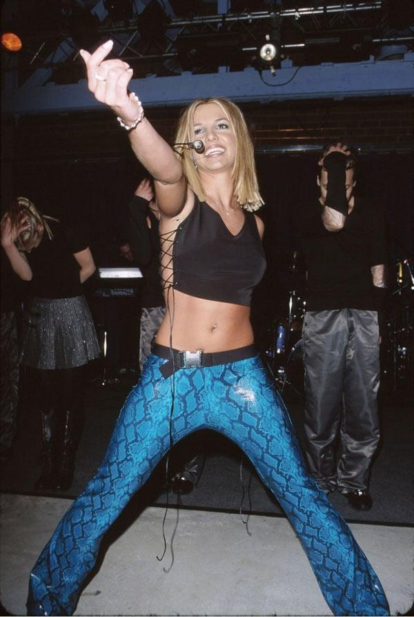 <p>Performing in a black lace-up crop top and blue snakeskin pants.</p>