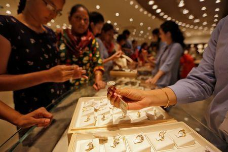 A sales person shows a gold ring to customers at a jewellery showroom during Dhanteras, a Hindu festival associated with Lakshmi, the goddess of wealth, in Ahmedabad