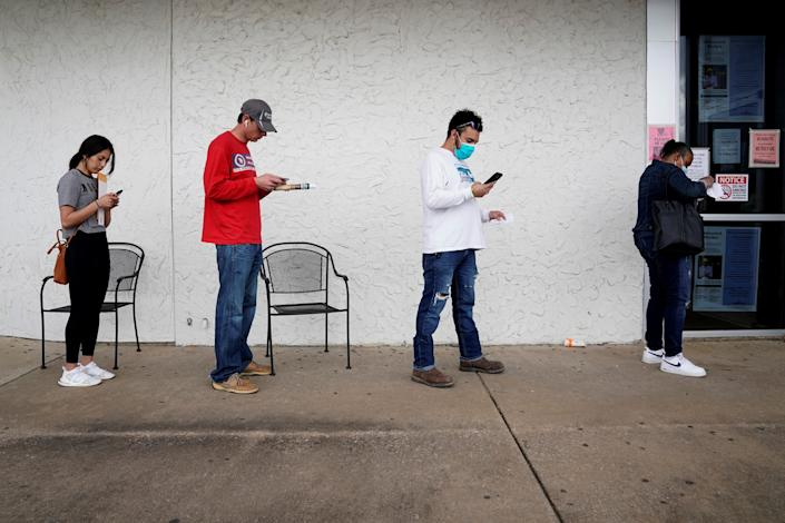 FILE PHOTO: People who lost their jobs wait in line to file for unemployment following an outbreak of the coronavirus disease (COVID-19), at an Arkansas Workforce Center in Fayetteville, Arkansas, U.S. April 6, 2020. REUTERS/Nick Oxford