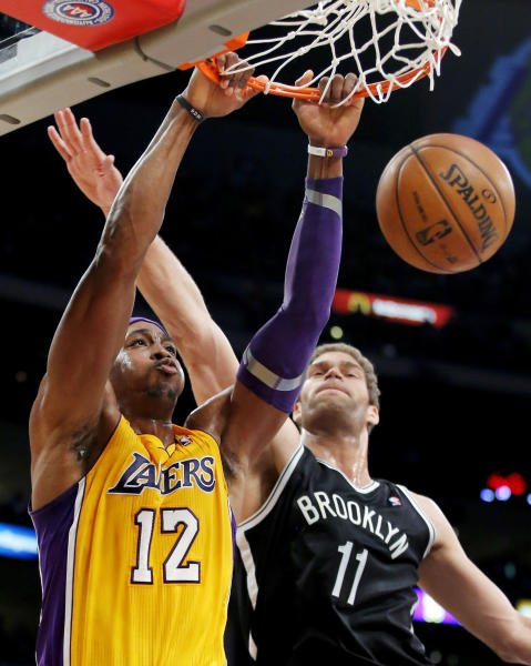 Los Angeles Lakers' Dwight Howard (12) dunks against Brooklyn Nets' Brook Lopez (11) in the first half of an NBA basketball game in Los Angeles, Tuesday, Nov. 20, 2012. (AP Photo/Jae C. Hong)