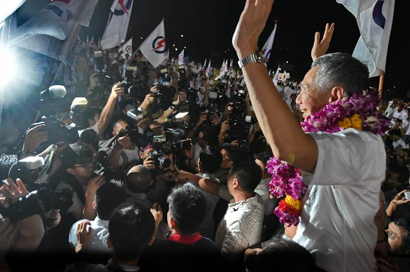 Singapore's Prime Minister Lee Hsien Loong, of the People's Action Party celebrates after winning the general election in Singapore on September 12, 2015. Singaporeans voted on September 11 in the most hotly contested election in the country's history after massive turnouts at opposition rallies boosted chances that a two-party system will emerge from half a century of domination by the ruling party. The People's Action Party (PAP), co-founded by the late independence leader Lee Kuan Yew and now led by his son, Prime Minister Lee Hsien Loong, is widely expected to retain a clear majority in the 89-seat parliament. AFP PHOTO / ROSLAN RAHMAN (Photo credit should read ROSLAN RAHMAN/AFP via Getty Images)