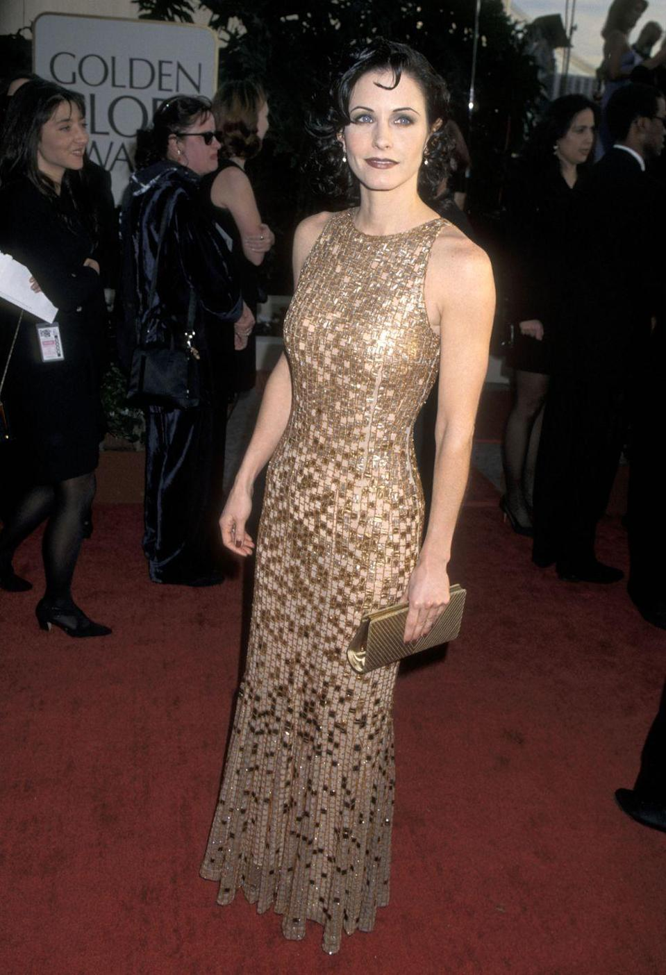 <p>Continuing the metallic trend into 1997, Courteney Cox glammed up the evening in this sleeveless gold dress.</p>