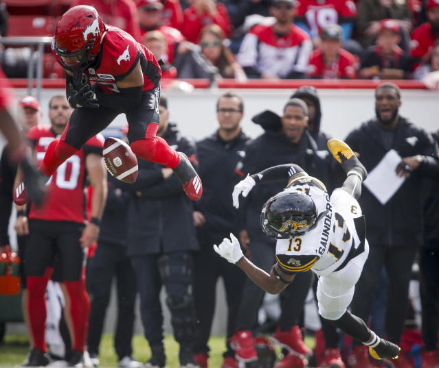 Hamilton Tiger-Cats' Jalen Saunders, right, and Calgary Stampeders' DaVaris Daniels try for the ball during first-half CFL football game action in Calgary, Alberta, Saturday, June 16, 2018. (Jeff McIntosh/The Canadian Press via AP)