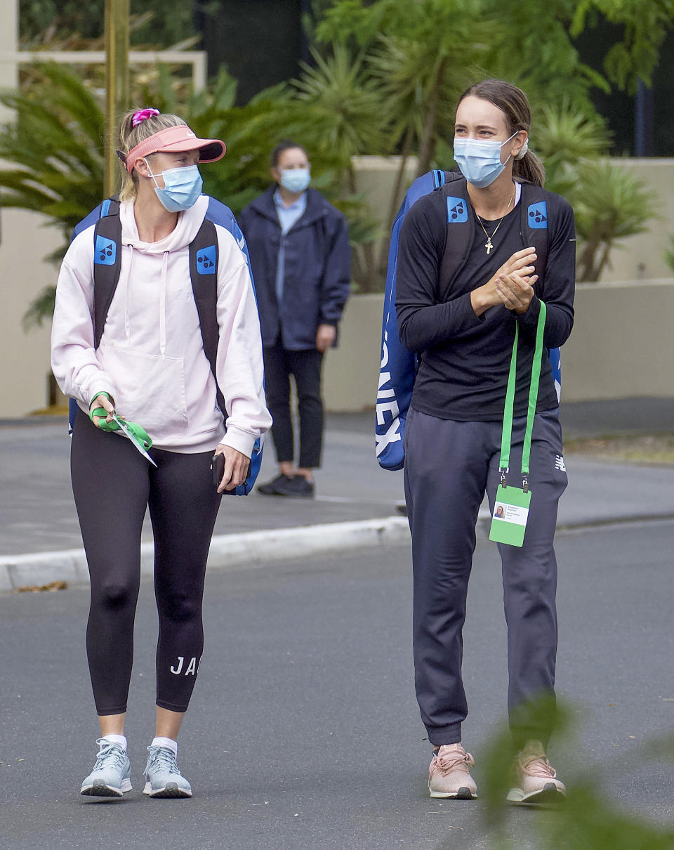 Unknown tennis players are escorted to their training session in Melbourne, Australia, Monday, Jan. 18, 2021.The number of players in hard quarantine swelled to 72 ahead of the Australian Open after a fifth positive coronavirus test was returned from the charter flights bringing players, coaches, officials and media to Melbourne for the season-opening tennis major. (Luis Ascui/AAP Image via AP)
