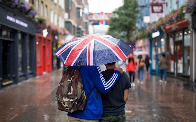 Tourists shelter from the rain in London under an umbrella featuring the Union Jack - © 2018 Bloomberg Finance LP