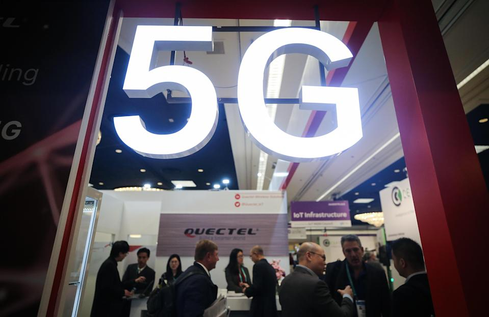 Attendees and workers chat beneath a 5G logo at the Quectel booth at CES 2020 at the Las Vegas Convention Center on January 8, 2020 in Las Vegas, Nevada. / Credit: Mario Tama  / Getty Images
