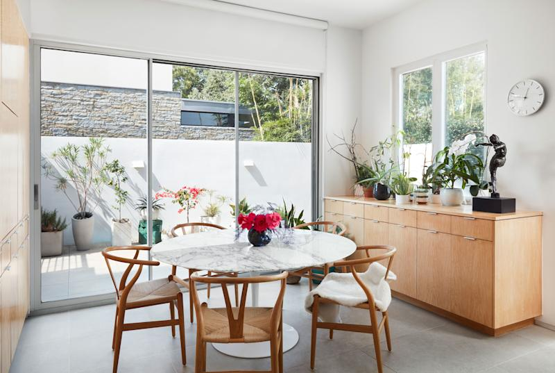 The couple kept to midcentury classics for the kitchen's fuss-free dining  area: a Saarinen Tulip table surrounded by Wegner Wishbone chairs. The sliding doors lead to a patio where the couple grills.