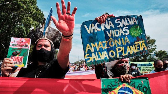 Demonstrators hold signs during a protest against President Jair Bolsonaro in Brasilia on May 29, 2021