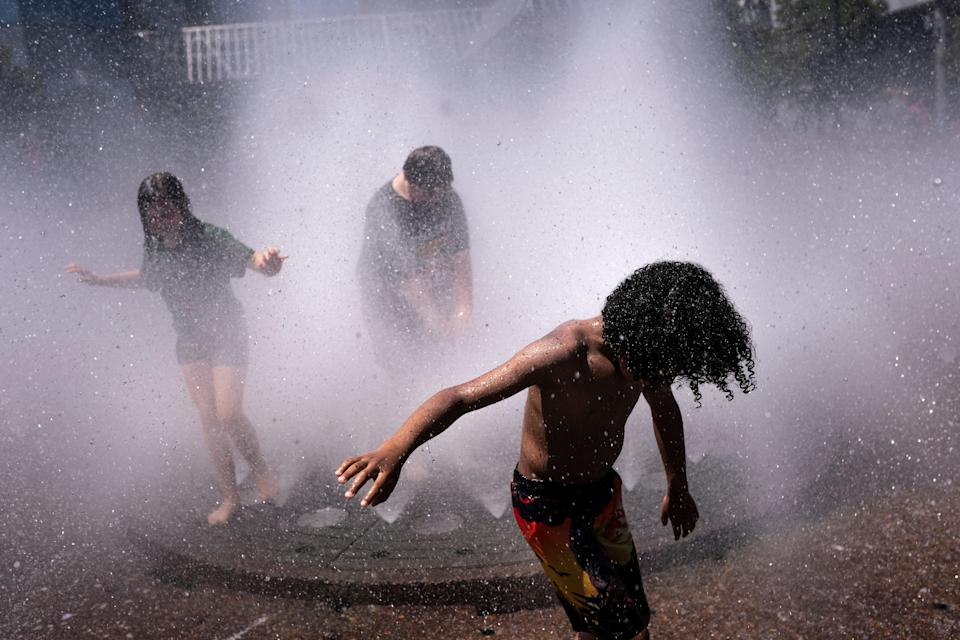 Children play in a fountain in  Portland, one of many places in Pacific Northwest where people struggled to stay cool (Getty Images)