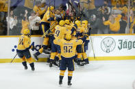 Nashville Predators players celebrate after Matt Duchene scored the winning goal against the Carolina Hurricanes during the second overtime in Game 3 of an NHL hockey Stanley Cup first-round playoff series Friday, May 21, 2021, in Nashville, Tenn. The Predators won 5-4. (AP Photo/Mark Humphrey)