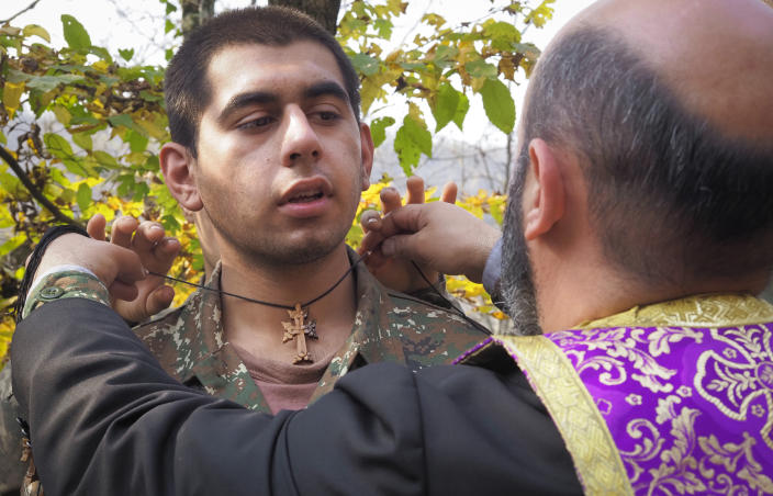 Priest Aristakes Hovhannisyan places a crucifix on an ethnic Armenian soldier during a baptism ceremony in a military camp near the front line during a military conflict in separatist region of Nagorno-Karabakh, Monday, Nov. 2, 2020. Fighting over the separatist territory of Nagorno-Karabakh entered sixth week on Sunday, with Armenian and Azerbaijani forces blaming each other for new attacks. (AP Photo)