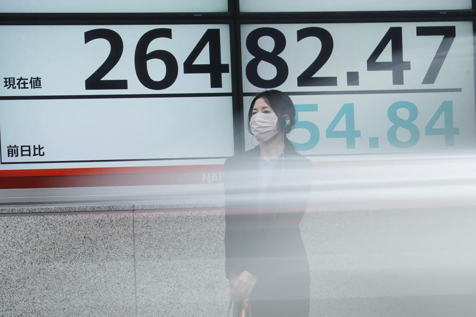 A woman wearing a protective face mask to help curb the spread of the coronavirus stands near an electronic stock board showing Japan's Nikkei 225 index at a securities firm as a car passing by Friday, Nov. 27, 2020, in Tokyo. Asian stock markets declined Friday as questions about the effectiveness of one possible coronavirus vaccine weighed on investor optimism. (AP Photo/Eugene Hoshiko)