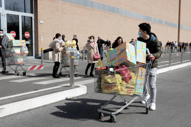 People wearing face masks queuing up at supermarkets to stock up on food and goods in Rome, Italy. (Credit: Simona Granati/Getty Images)