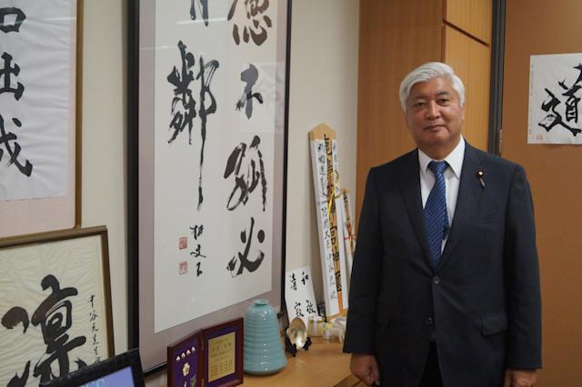<p>Former Japanese Defense Minister Gen Nakatani stands in his office beside framed calligraphy with moral teachings and instructions. One work on display says that a person of virtue is not isolated and must have some companions. Another piece says the unvarnished truth is better than a cunning ruse and that honesty is the best policy. (Photo: Michael Walsh/Yahoo News) </p>