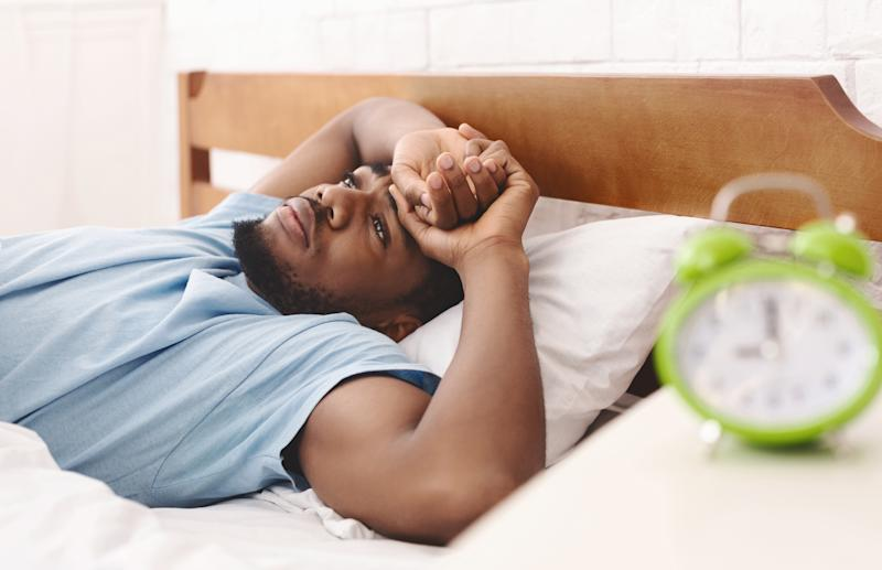 Black man in bed suffering from insomnia and sleep disorder
