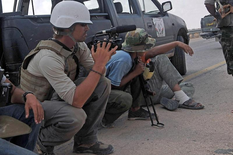 Freelance reporter James Foley (L) is pictured on the highway between the airport and the West Gate of Sirte, Libya on August 19, 2014 (AFP Photo/Aris Messinis )