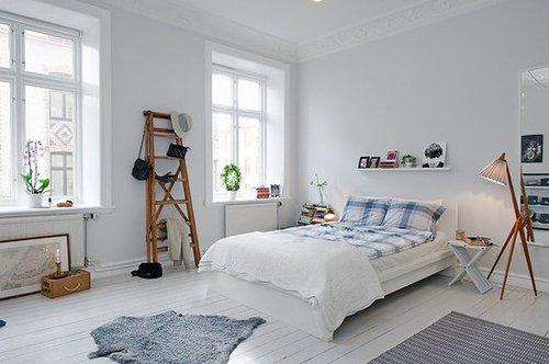 Wooden accents, textured rugs, and patterned fabrics add warmth against the all-white base of this bedroom in an eclectic Swedish apartment. Source: Alvhem Estate & Interior