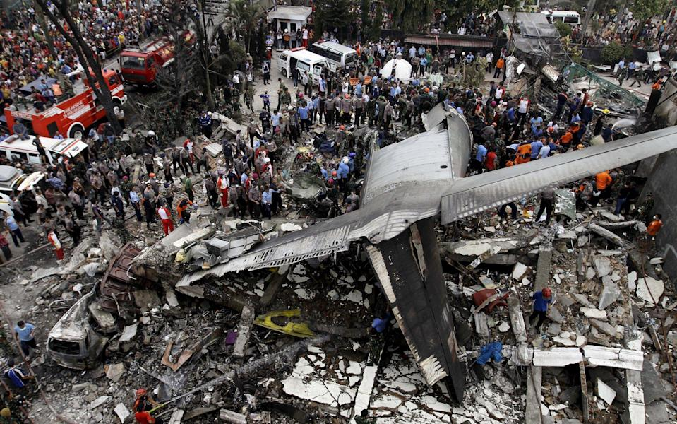 Security forces and rescue teams examine the wreckage of an Indonesian military C-130 Hercules transport plane after it crashed into a residential area in the North Sumatra city of Medan, Indonesia, June 30, 2015. - RONI BINTANG/Reuters