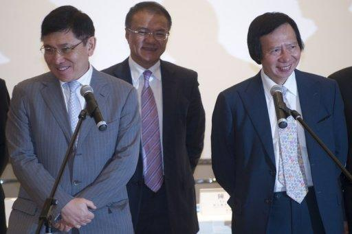 Co-chairman and Managing Directors of Sun Hung Kai Properties Raymond Kwok (L) and Thomas Kwok (R) react