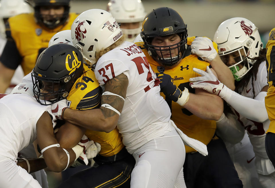 California's Christopher Brown Jr., left, rushes against Washington State's Justus Rogers (37) in the first half of an NCAA college football game Saturday, Nov. 9, 2019, in Berkeley, Calif. (AP Photo/Ben Margot)