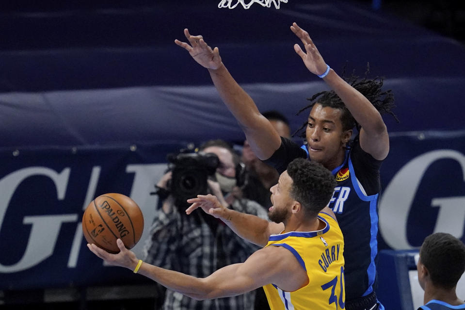Golden State Warriors guard Stephen Curry (30) goes to the basket defender by Oklahoma City Thunder center Moses Brown, right, in the first half of an NBA basketball game Wednesday, April 14, 2021, in Oklahoma City. (AP Photo/Sue Ogrocki)
