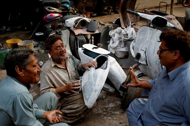 <p>Akram (C) applies coating on Vespa scooter parts, as he chats with owners of Vespa scooters Farrukh Shahbaz (L) and Matiur Rehman outside his workshop in Karachi, Pakistan Feb. 24, 2018. (Photo: Akhtar Soomro/Reuters) </p>