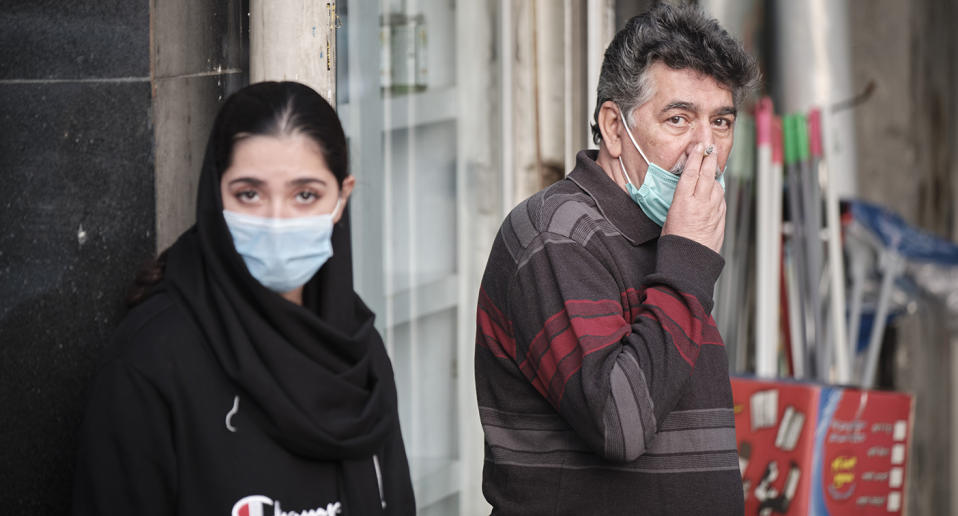 A man and a woman seen wearing coronavirus face masks in a street in Iran.
