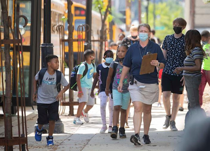 Teacher Erin Bailey walks students to their buses they're released early due to extreme heat at Golda Meir School in Milwaukee on Aug. 25.