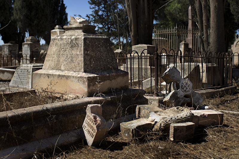 In this Monday, Oct. 7, 2013 photo, a damaged grave after a vandal attack is shown in the Protestant Cemetery of Mt. Zion, Jerusalem. Christian leaders in the Holy Land are up in arms over what Curiously, is not the first time the Protestant cemetery has been attacked. About 100 years ago, the American consul to Jerusalem dug up graves in the cemetery belonging to members of the American Colony, a group of Christians from the U.S. who moved to Jerusalem for religious reasons – but whom the consul said were involved in cult-like activities, said Israeli researcher Nirit Shalev-Khalifa. (AP Photo/Bernat Armangue)