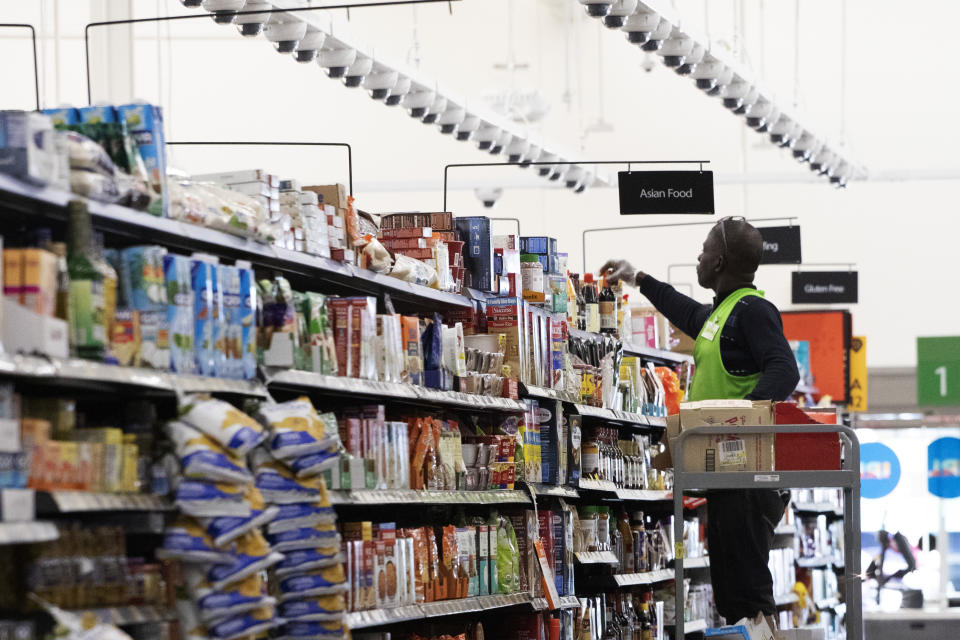 A Walmart associate arranges items on a shelf at a Walmart Neighborhood Market, Wednesday, April 24, 2019, in Levittown, N.Y. The cameras that are suspended above are a key feature of a living lab inside this 50,000-square-foot store. Walmart envisions using these cameras, combined with other technology like sensors on shelves to get the best picture of what's going on in the store in real time so its workers can quickly react to replenish the products or fix other problems. (AP Photo/Mark Lennihan)