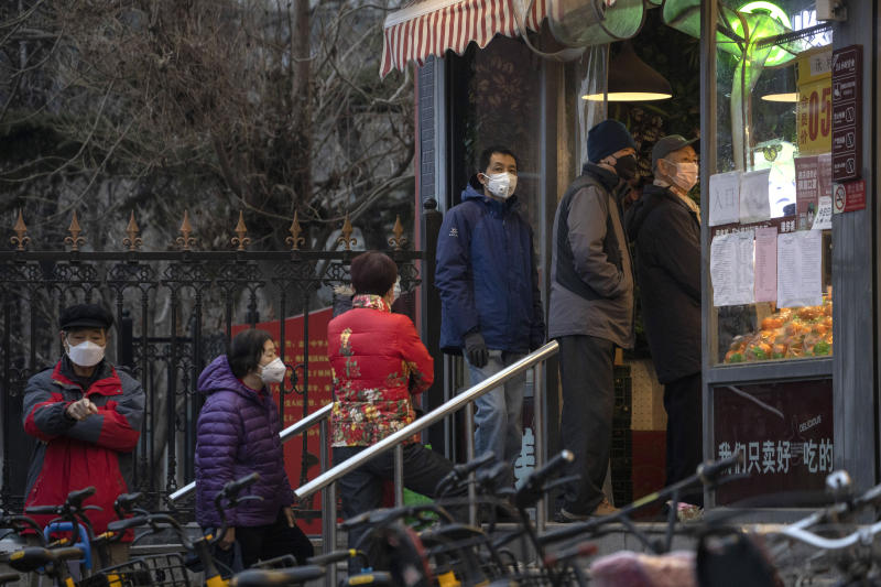 Residents wear masks and line up to enter a supermarket which is controlling the numbers of shoppers in Beijing, China on Tuesday, Feb. 25, 2020. The new virus took aim at a broadening swath of the globe Monday, with officials in Europe and the Middle East scrambling to limit the spread of an outbreak that showed signs of stabilizing at its Chinese epicenter but posed new threats far beyond. (AP Photo/Ng Han Guan)
