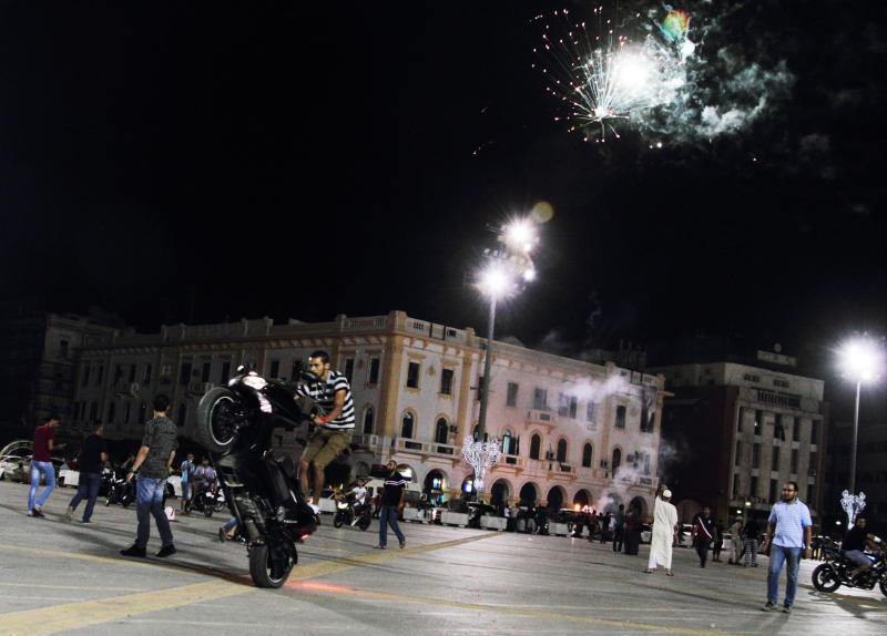 In this Saturday, Oct. 20, 2012 photo, Libyans celebrate the first anniversary of the capture and killing of former dictator Moammar Gadhafi at Martyrs Square in Tripoli, Libya. (AP Photo/Gaia Anderson)