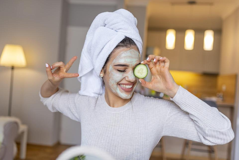 Portrait of a happy caucasian woman using natural secrets to do a skin care. Natural homemade facial masks. Beautiful young woman applying avocado facial mask with cucumber