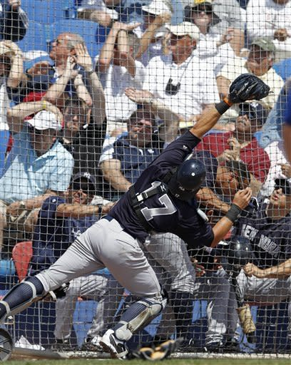 New York Yankees catcher Francisco Cervelli (17) reaches to field Adam Lind's pop out in foul territory as Yankees third baseman Alex Rodriguez runs for cover and Yankees manager Joe Girardi watches during the fourth inning of their spring training baseball game against the Toronto Blue Jays in Dunedin, Fla., Wednesday, March 14, 2012. (AP Photo/Kathy Willens)