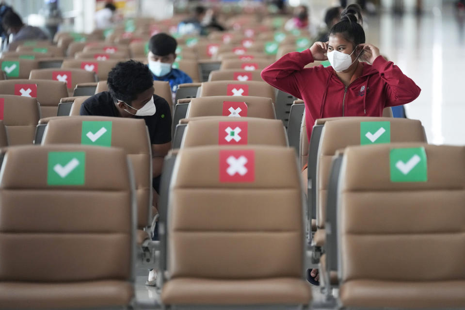 Passengers sit spaced apart while wearing face masks to help curb the spread of the coronavirus at Suvarnabhumi airport in Bangkok, Thailand, Wednesday, July 21, 2021. The Civil Aviation Authority of Thailand has ordered a halt to all domestic flights operating from the most severely affected provinces effective Wednesday. Exceptions are allowed for flights to destinations that are part of a plan that allows vaccinated travelers from abroad to stay for two weeks on popular islands such as Phuket and Samui without quarantine confinement. (AP Photo/Sakchai Lalit)