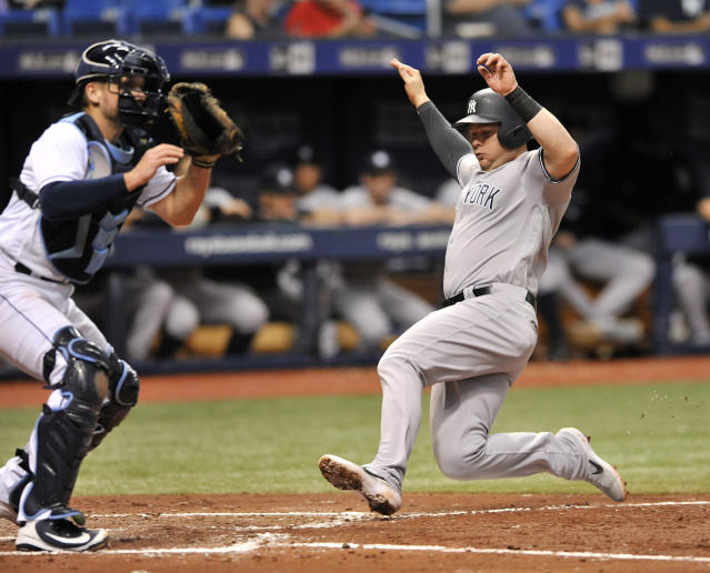 Tampa Bay Rays catcher Adam Moore waits for the throw as New York Yankees' Luke Voit, right, scores on Miguel Andujar's sacrifice fly ball to right filed during the third inning of a baseball game Tuesday, Sept. 25, 2018, in St. Petersburg, Fla. (AP Photo/Steve Nesius)