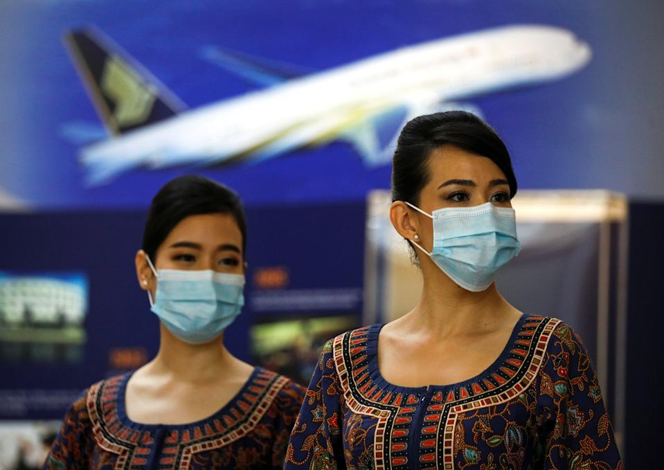 Cabin crew wait for participants during a guided tour at the Singapore Airlines Training Centre in Singapore November 21, 2020. The airlines offered tours of its training centre and flight simulator experiences as part of a series of initiatives to try an re-engage customers who have not been able to travel due to the coronavirus disease (COVID-19) pandemic.  REUTERS/Edgar Su