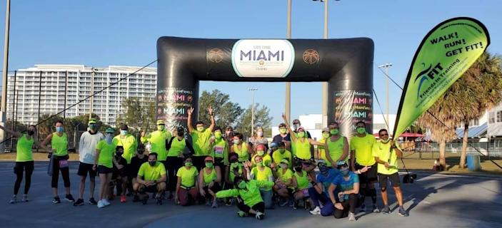 Marathoner Marcela Todd sits in front of her Friends in Training group in January 2021 after they ran the half marathon distance of the #VirtuallyMiamiFamous race at George English Park in Fort Lauderdale.