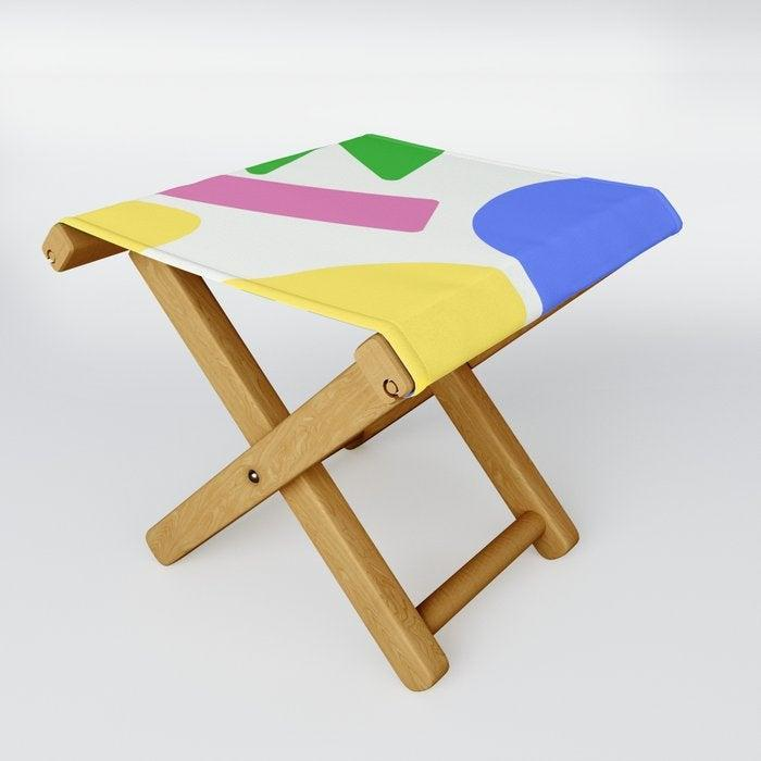 """<h2>Society6 Primary Colors Folding Stool</h2><br>Not only is this vibrant statement stool uniquely designed by talented independent artist, <a href=""""https://society6.com/oland"""" rel=""""nofollow noopener"""" target=""""_blank"""" data-ylk=""""slk:Kalypso Harvey"""" class=""""link rapid-noclick-resp"""">Kalypso Harvey</a>, but it also happens to be water-resistant and fold-up-able (which means storage couldn't be easier). <br><br>Use it as transportable park seating, a footrest, or add a tray and use it as an accent table, plant stand — or, drag it up onto the kitchen counter for a DIY standing desk extension. <br><br><strong>KalypsoHarvey</strong> Primary colors Folding Stool, $, available at <a href=""""https://go.skimresources.com/?id=30283X879131&url=https%3A%2F%2Fsociety6.com%2Fproduct%2Fprimary-colors2920489_folding-stool"""" rel=""""nofollow noopener"""" target=""""_blank"""" data-ylk=""""slk:Society6"""" class=""""link rapid-noclick-resp"""">Society6</a>"""