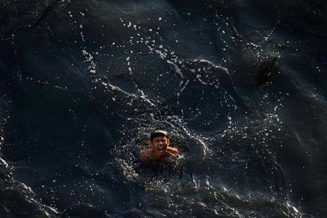 A boy swims in the polluted water of a canal in Bangkok, Thailand, March 20, 2018. REUTERS/Athit Perawongmetha TPX IMAGES OF THE DAY