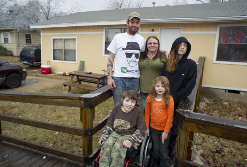 Lori Latch, back row center, with her husband Chad, left rear, son Marcus, right rear, son Eric, front left, and daughter Ruby, front right, at their home in North Little Rock, Ark., Tuesday, Feb. 4, 2014. Lori Latch, 35, said she was looking forward to having health insurance for the first time since she was a teenager. She and her husband, who is self-employed, have racked up more than $5,000 in bills for emergency room visits. Arkansas' plan for expanding Medicaid by buying private insurance policies for the poor instead of adding them to the rolls was heralded as a model for convincing more Republican-leaning states to adopt a key part of President Barack Obama's health care overhaul. But less than a year after its approval, the program that has extended health insurance to 83,000 people is on the brink of being abandoned. (AP Photo/Brian Chilson) (AP Photo/Brian Chilson)