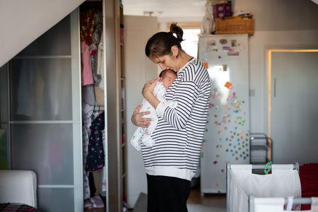 Maria, 31, holds her baby daughter Ioana, who is less than a week old, at their home in London, Britain, February 3, 2019. REUTERS/Alecsandra Dragoi