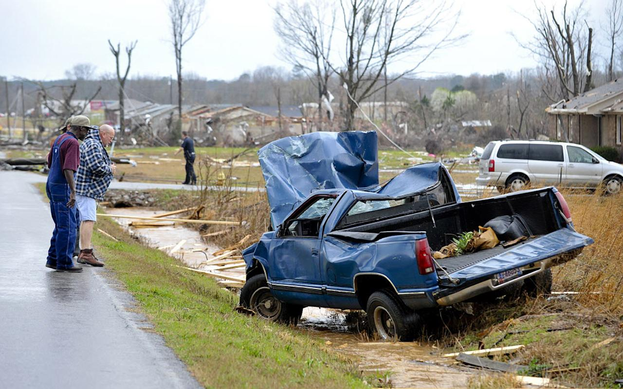 People look at a truck that was blown off the road by debris from a reported tornado that passed through the Harvest, Ala., area Friday, March 2, 2012. (AP Photo/The Huntsville Times, Bob Gathany)