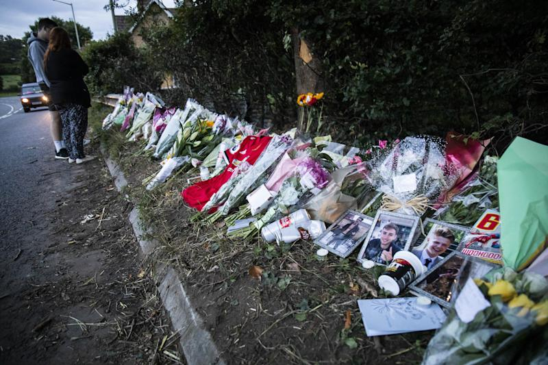 People pay their respects at a memorial for four men who died in a car accident on the A4. (SWNS)