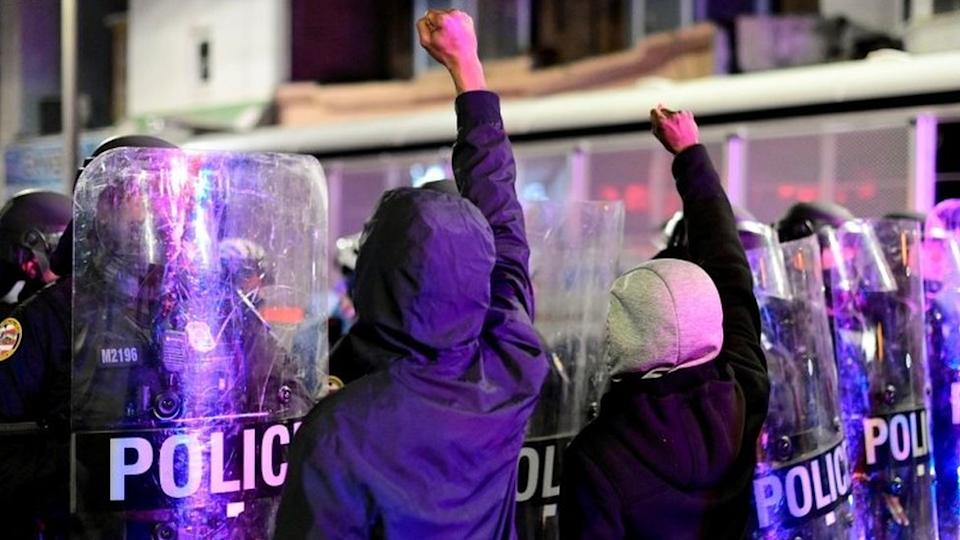 Protesters stand in front of a police barricade