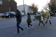 From left, Peter Taffs, Marcie Taffs, 14, Juno Taffs, 11, and Clare Van Loenen walk across the street after buying a tree from Frank Pichel's tree lot, Sunday, Dec. 6, 2020, in Richmond, Va. A Virginia man has found a way to use Charlie Brown-style Christmas trees to benefit a middle school that provides scholarships for students from an impoverished area. (AP Photo/Will Newton)