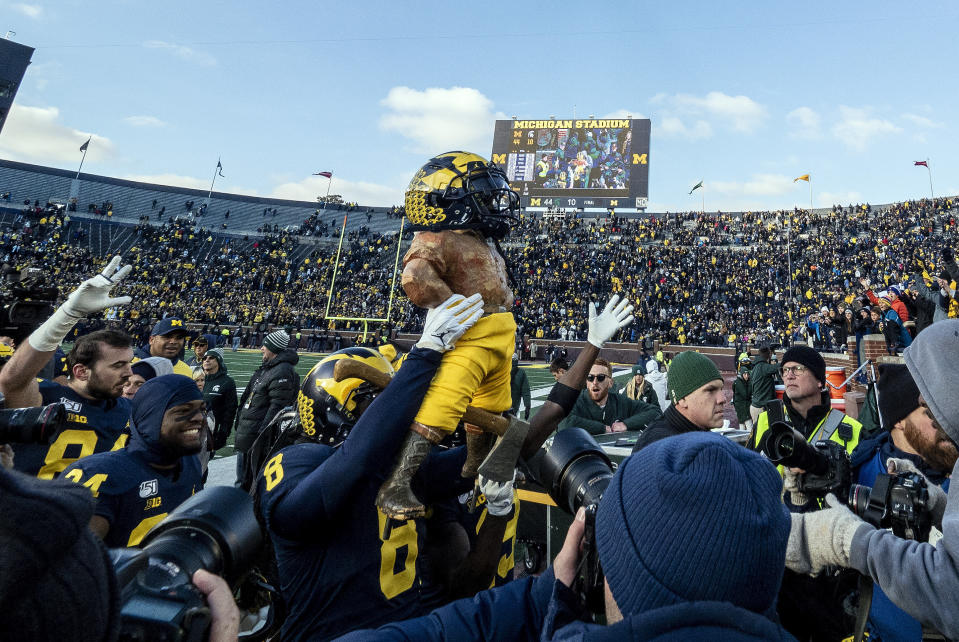 Michigan linebacker Devin Gil (8) lifts up the Paul Bunyan Trophy, dressed with a Michigan helmet and maize-colored pants, after an NCAA college football game against Michigan State in Ann Arbor, Mich., Saturday, Nov. 16, 2019. Michigan won 44-10. (AP Photo/Tony Ding)