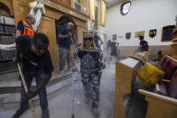 People clean debris from a damaged synagogue after it was hit by a rocket fired from the Gaza Strip, in Ashkelon, Israel, Sunday, May 16, 2021. (AP Photo/Tsafrir Abayov)
